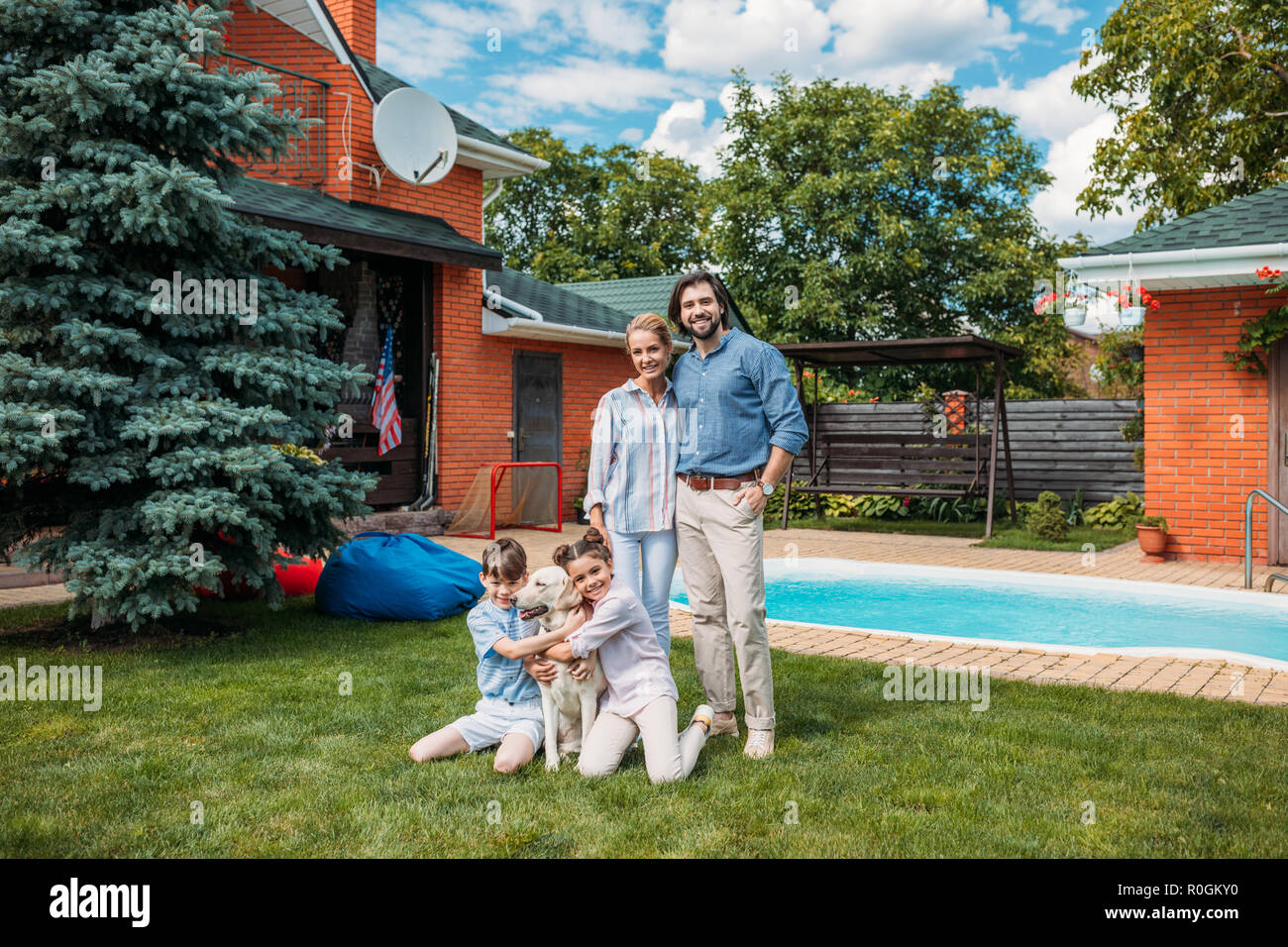 cheerful family with labrador dog looking at camera while spending time on backyard of country house on summer day - Stock Image