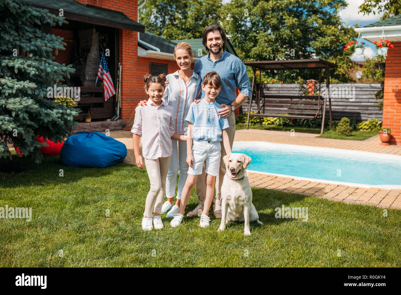 cheerful family with labrador dog looking at camera while standing on backyard of country house on summer day - Stock Image