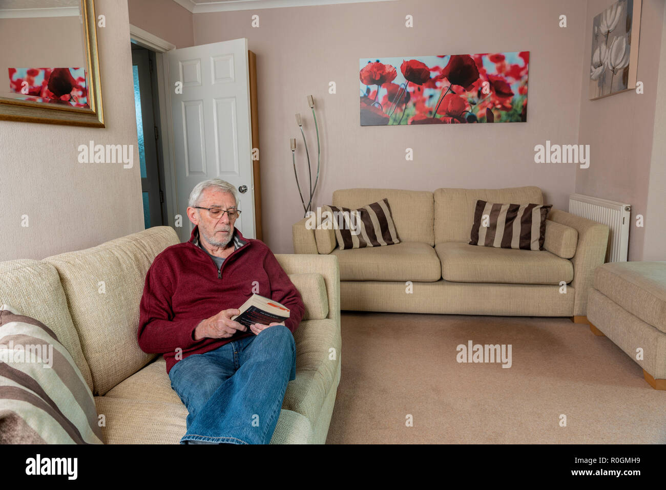 Senior man sitting alone on sofa, grieving after losing a loved one. Loneliness sad and sadness. - Stock Image