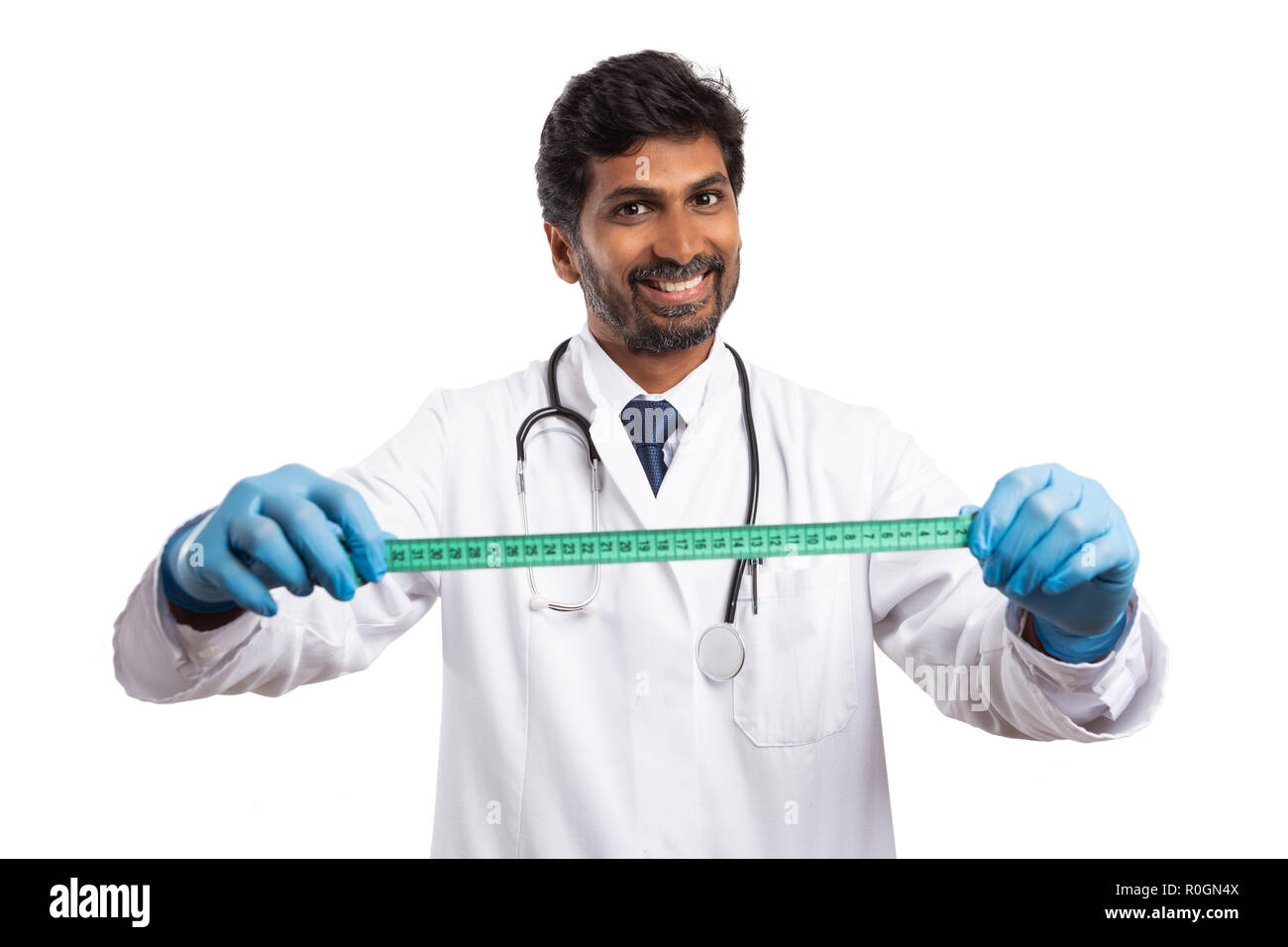 Indian doctor man measuring body size with tape isolated on white studio background - Stock Image