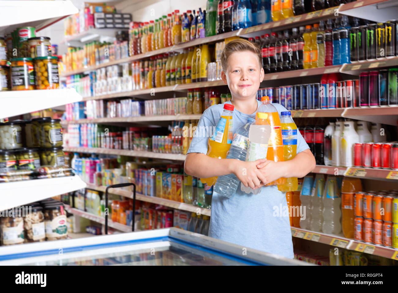 Portrait of happy cheerful positive smiling preteen boy with purchases in supermarket - Stock Image
