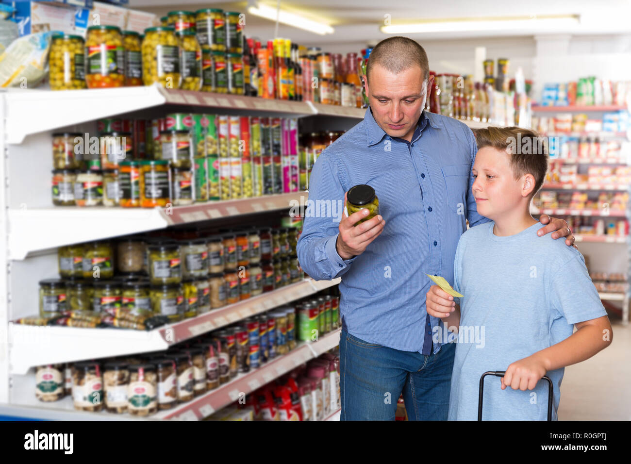 portrait of father and boy choosing goods with shopping list in