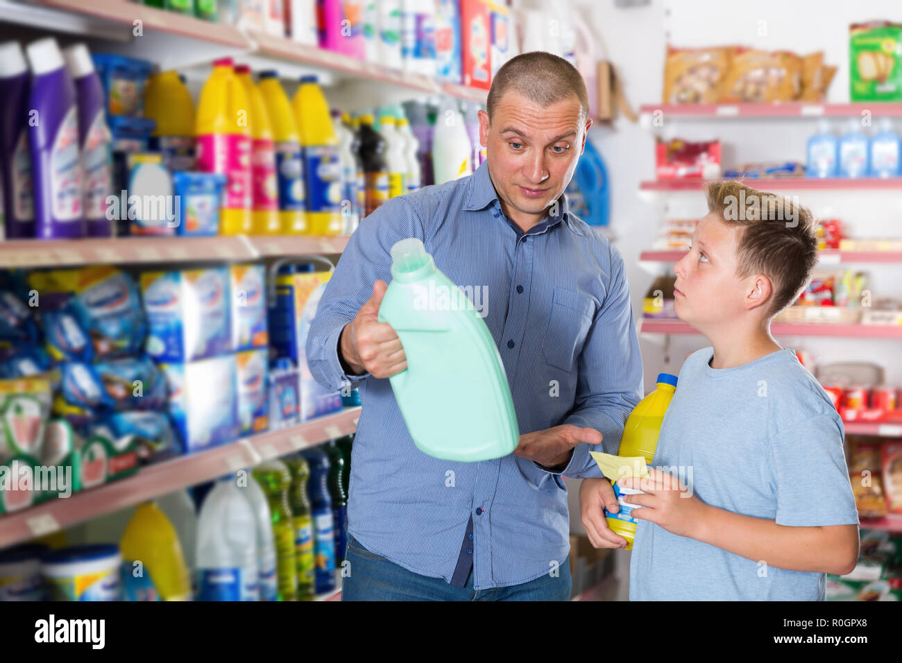 man and boy buying household chemicals with shopping list in