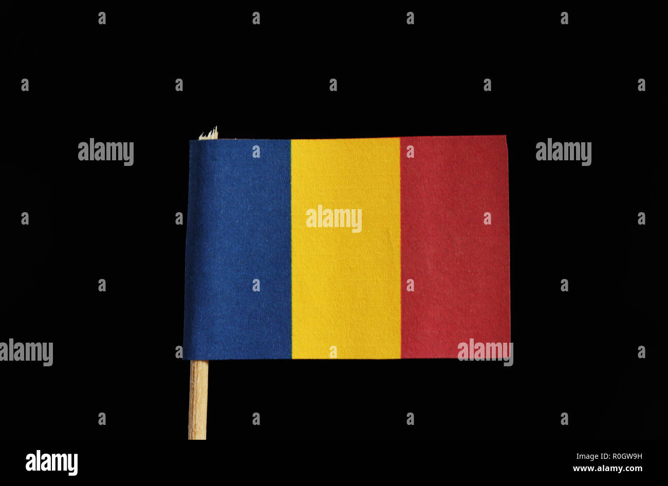 A national flag of Chad on toothpick on black background. A vertical tricolor of blue, gold and red - Stock Image