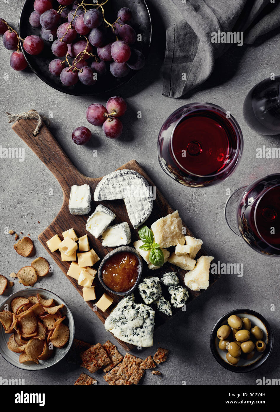 Cheese Plate Served With Red Wine Olives Grapes Jam And Bread Snacks On Gray Marble Background Top View Stock Photo Alamy