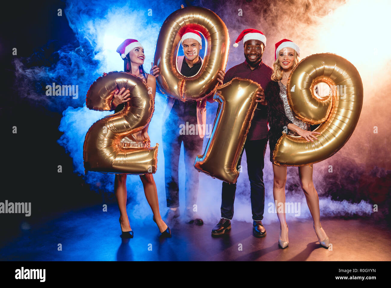 2eb168507047d multicultural friends in santa hats holding 2019 new year golden balloons  on black with smoke and backlit