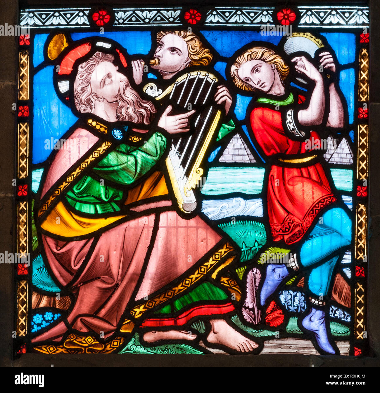 Hereford Cathedral, UK. Stained glass window showing King David playing the harp, with other musicians - Stock Image