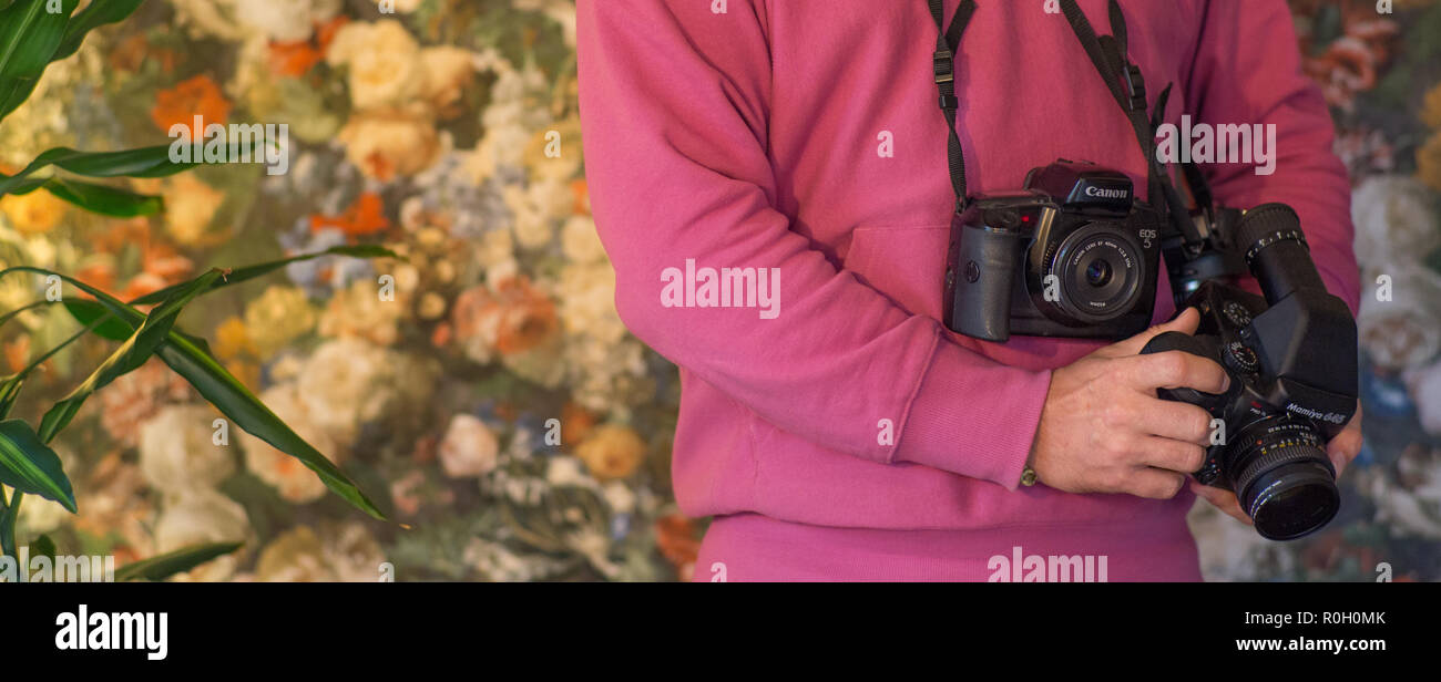 Self portrait of photographer holding analog cameras - Stock Image
