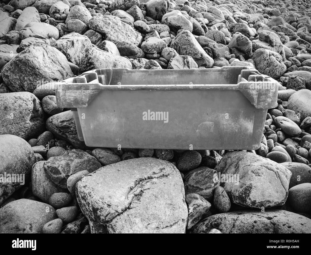 Dangerous rubbish on a stony beach.  Photo showing pollution problem. Dangerous garbage ejected from the sea on remote beaches. Stock Photo