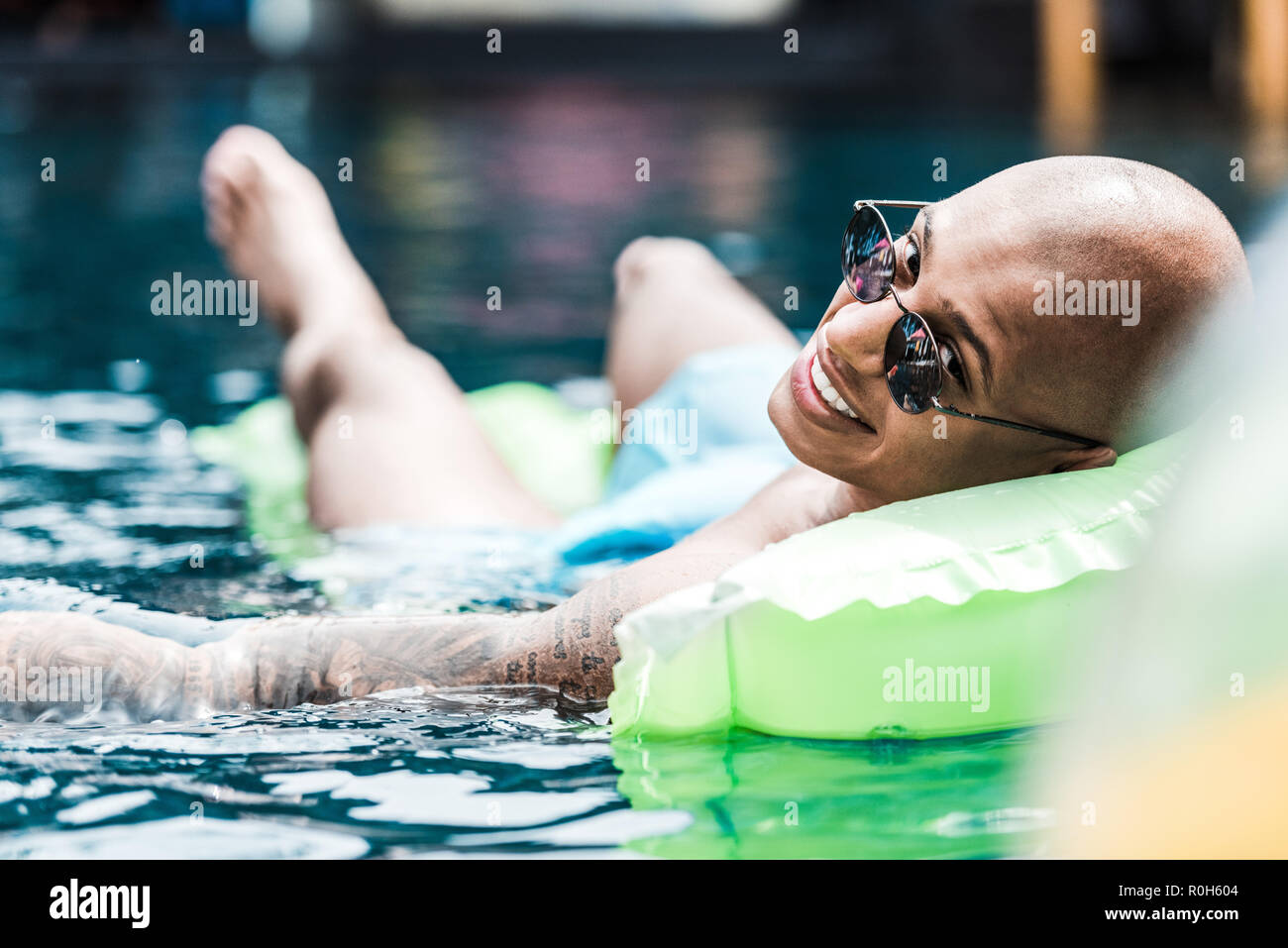 smiling man resting on inflatable mattress looking at camera in swimming pool - Stock Image