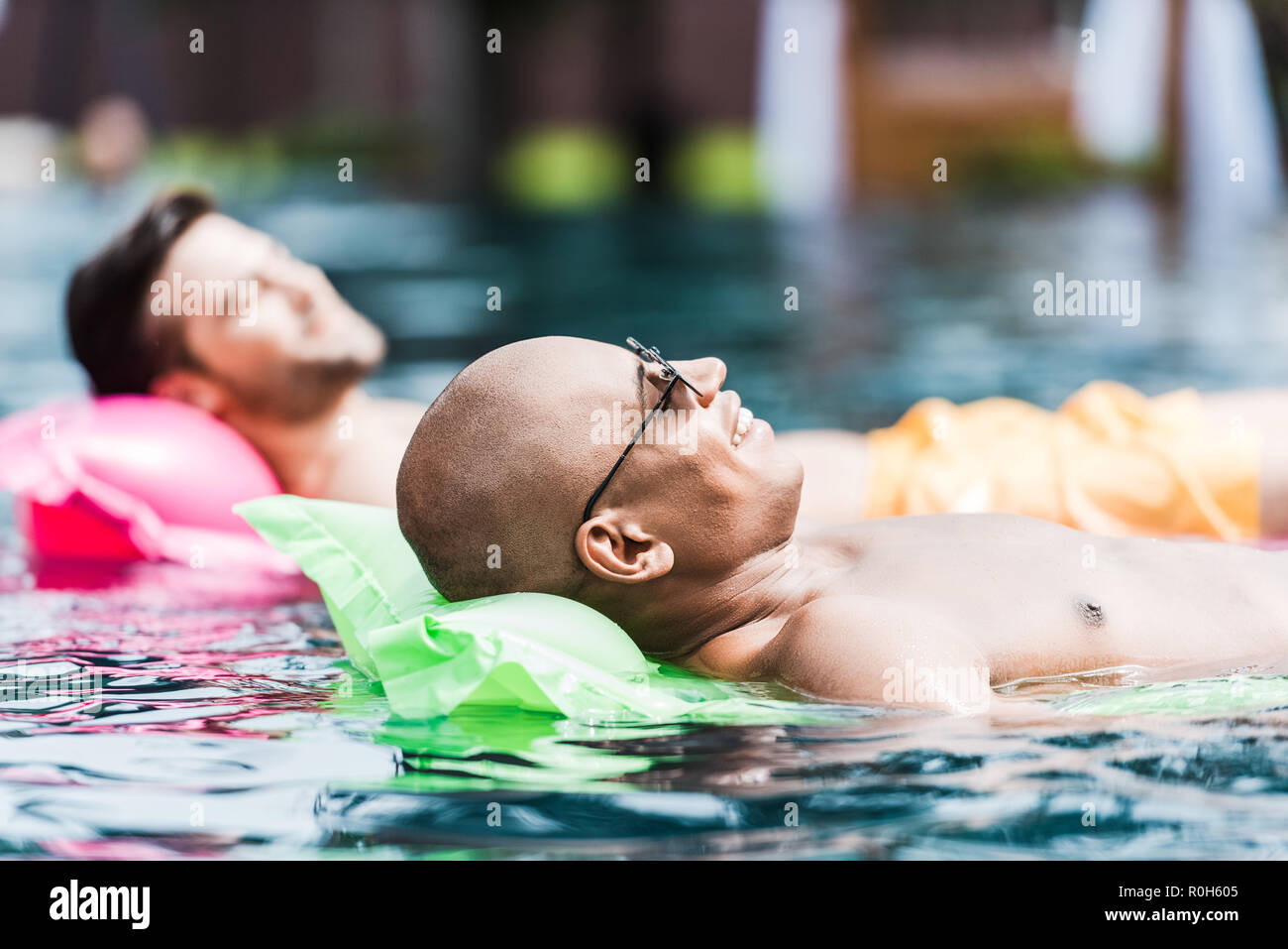 happy male friends resting and having sunbath on inflatable mattresses in swimming pool - Stock Image