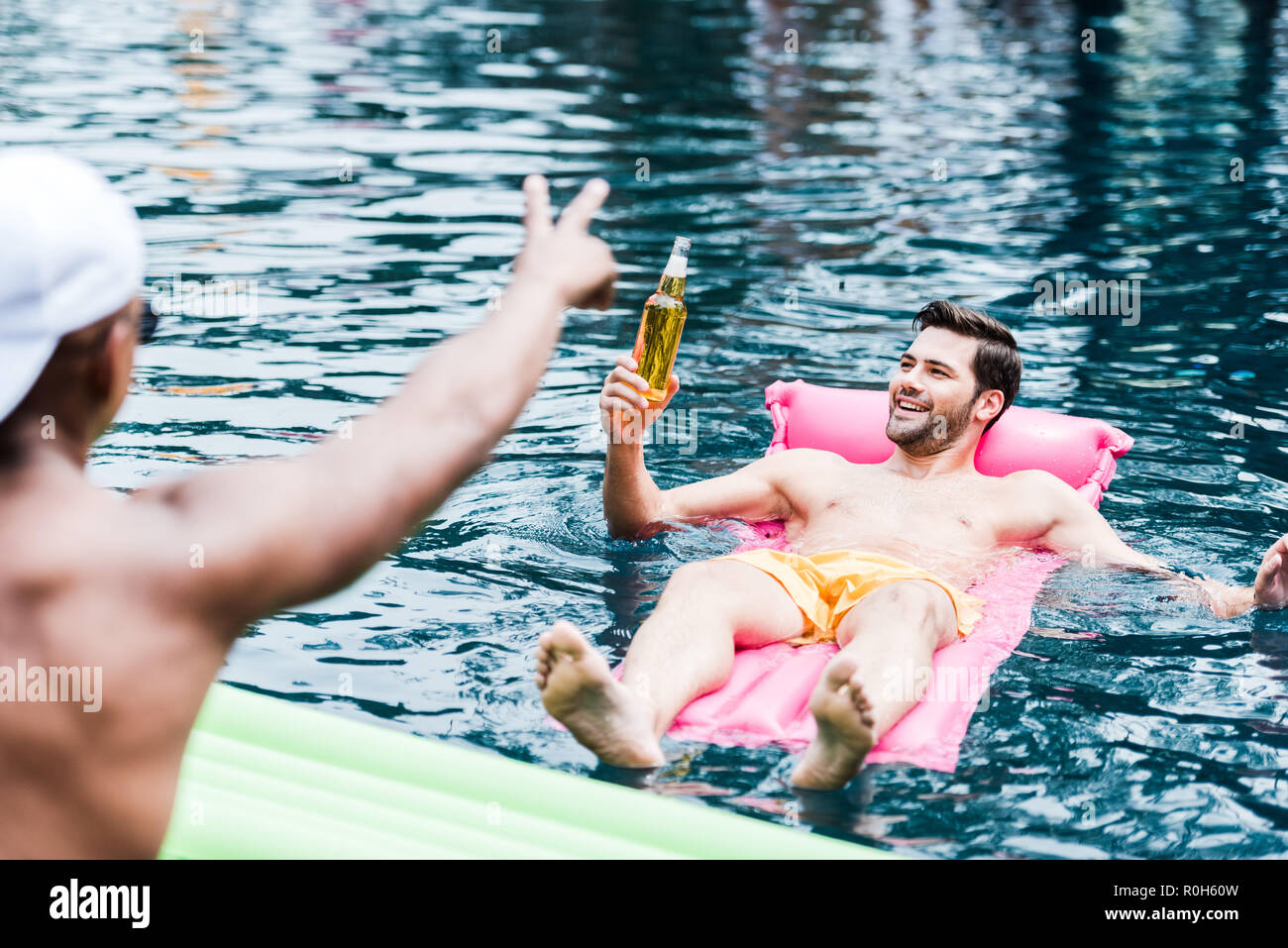 smiling man with beer resting on inflatable mattress in swimming pool while his friend gesturing by fingers at poolside - Stock Image