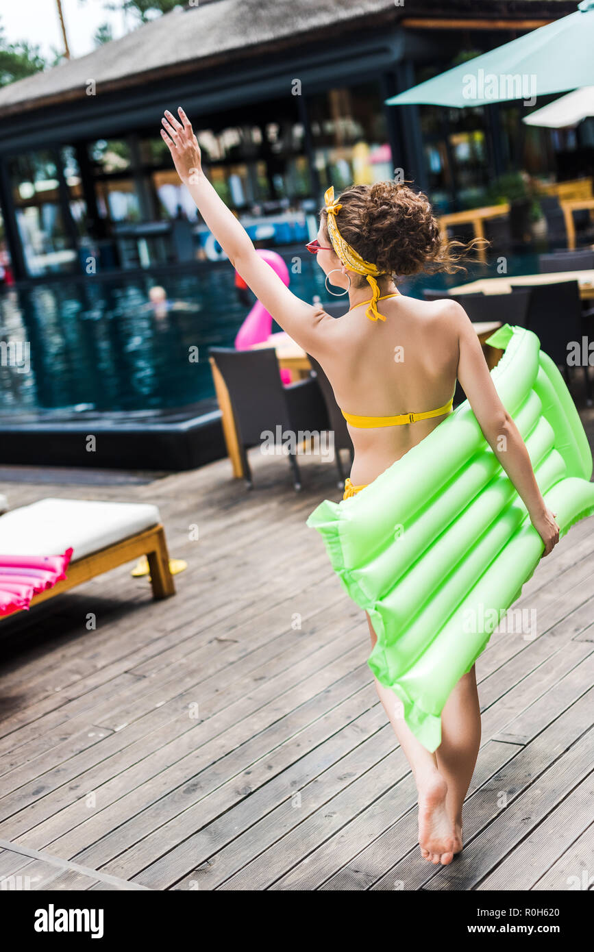 back view of girl in swimsuit walking with inflatable mattress near swimming pool and waving hand - Stock Image
