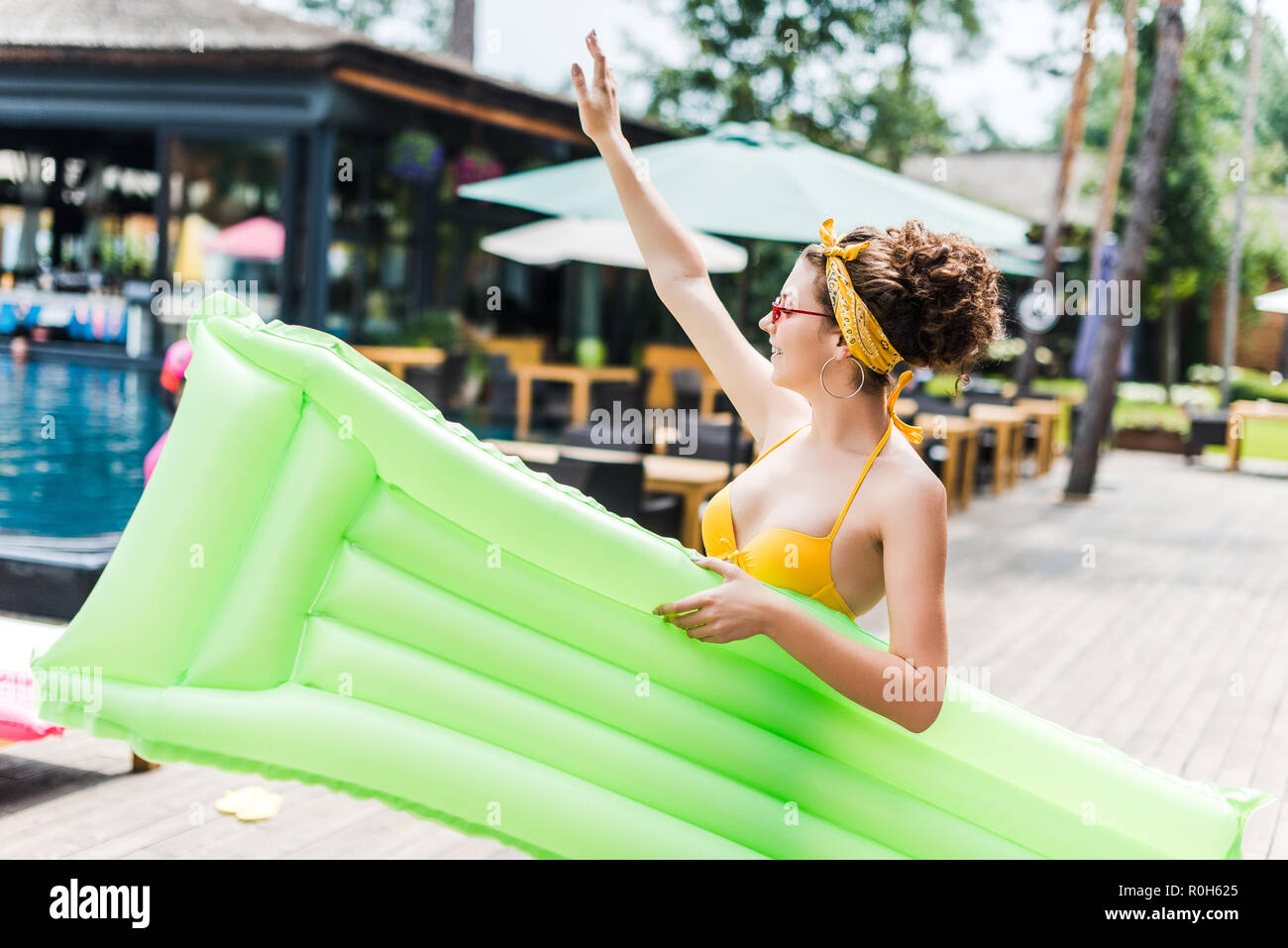 girl in swimsuit walking with inflatable mattress near swimming pool and waving hand - Stock Image