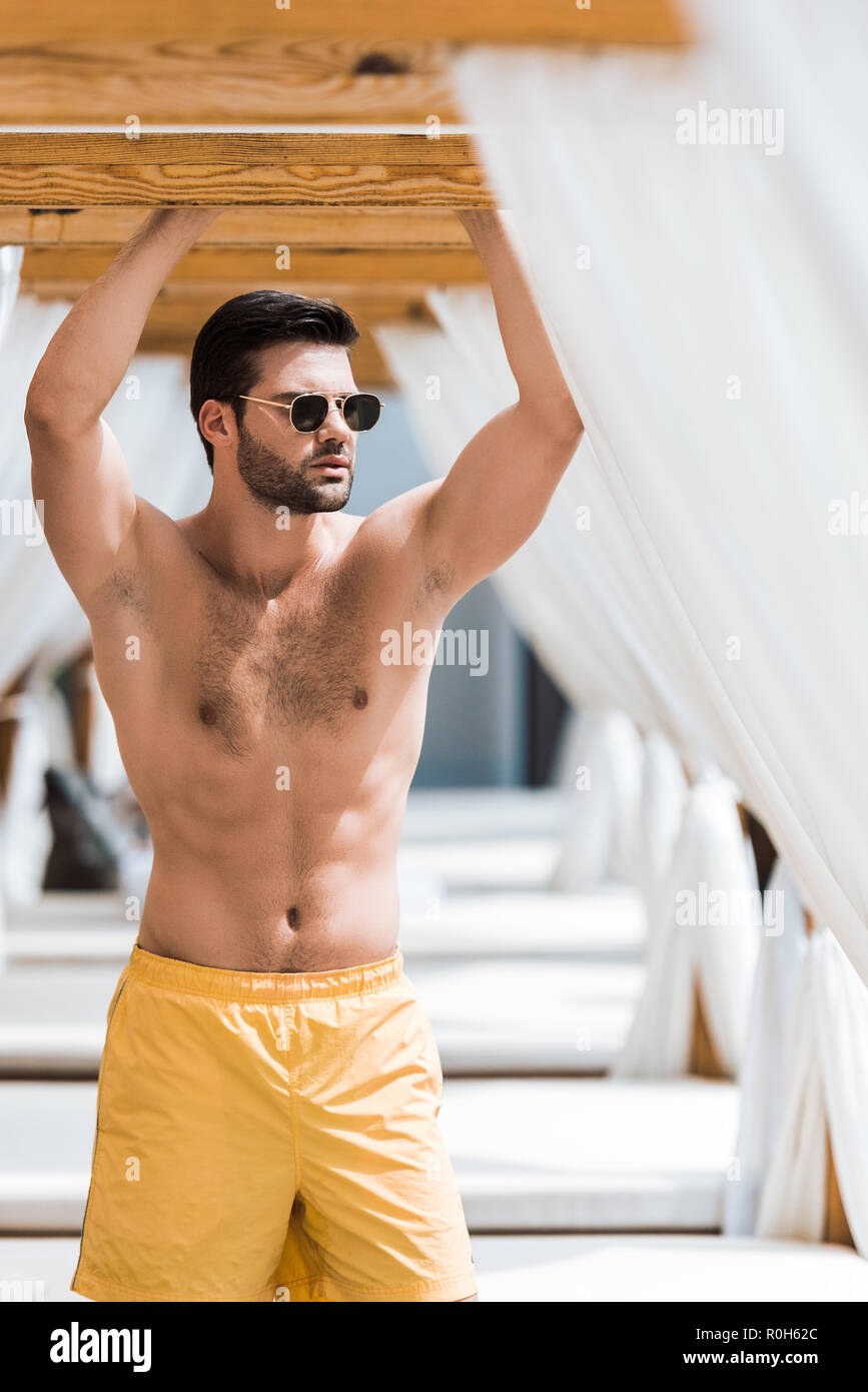 handsome shirtless man in sunglasses standing near sun loungers - Stock Image