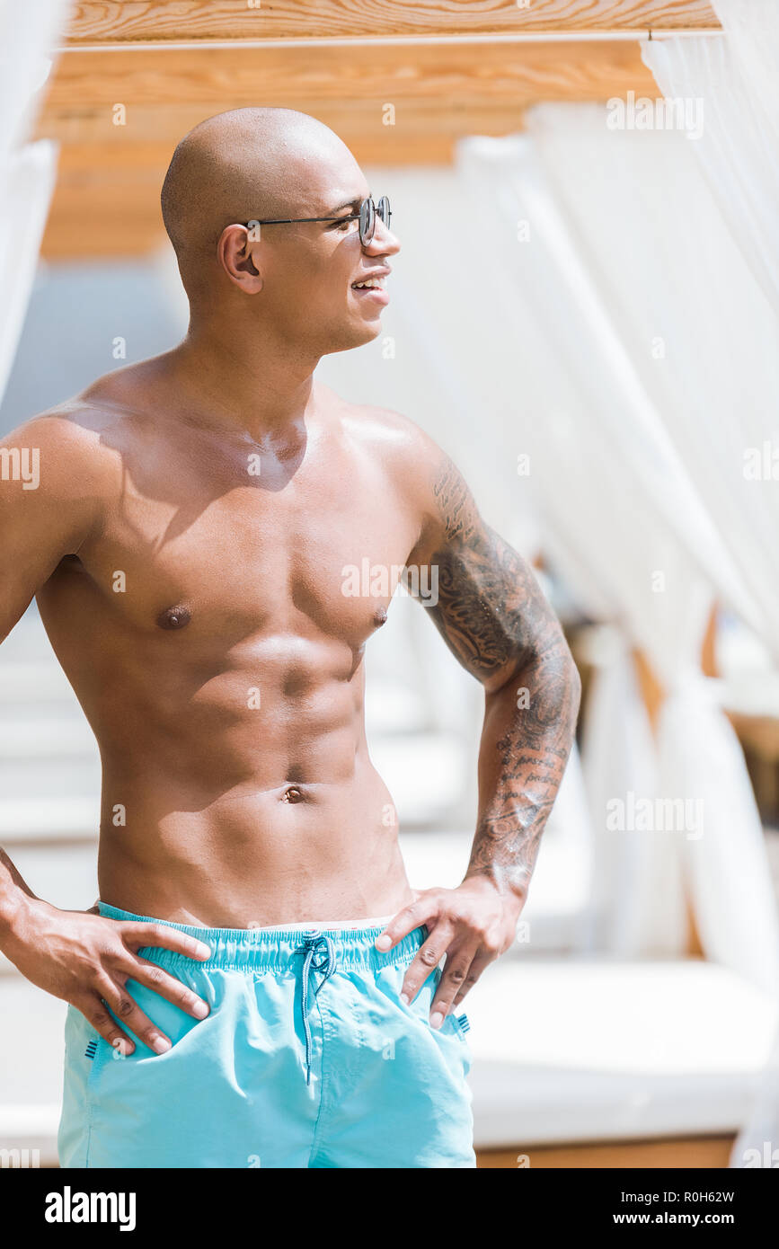 shirtless tattooed muscular man standing near sun loungers and looking away - Stock Image