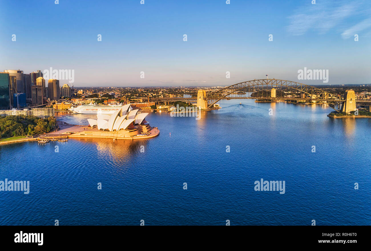 Calm Sydney harbour in early morning hour with soft sun light on massive steel arch of the Sydney Harbour bridge connecting city CBD towers and waterf - Stock Image
