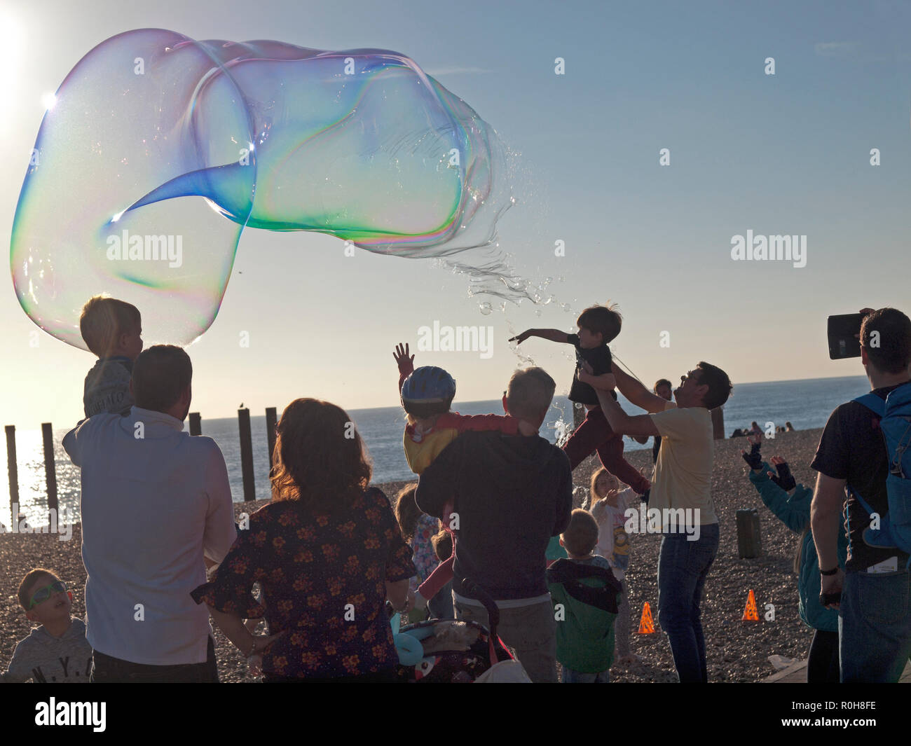 Large bubbles being blown for the amusement of children on the beach at Brighton - Stock Image