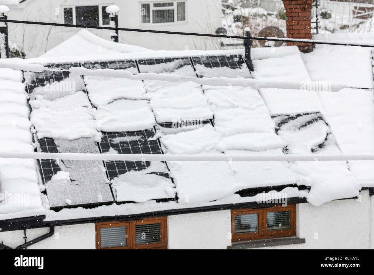 Solar panels with snow cover sliding off, Llanfoist, Wales, UK - Stock Image
