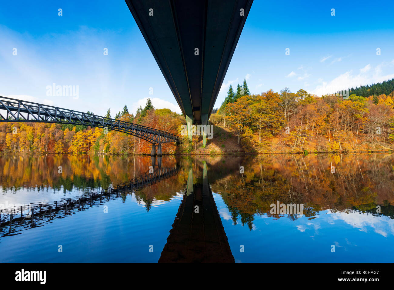 Spectacular late autumn tree colours and twin bridges are reflected in the waters of Loch Faskally in Pitlochry, Perthshire, Scotland, UK. - Stock Image