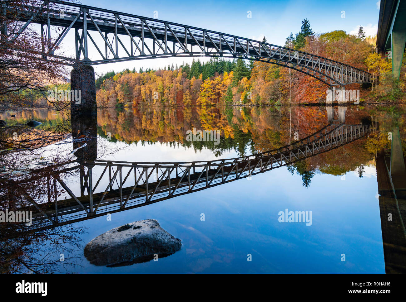 Spectacular late autumn tree colours and bridge is  reflected in the waters of Loch Faskally in Pitlochry, Perthshire, Scotland, UK. - Stock Image