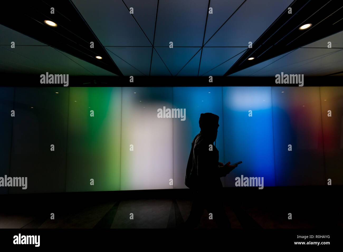 Young man walking using phone in futuristic modern sci-fi moody dark tunnel background in city London lights Stock Photo