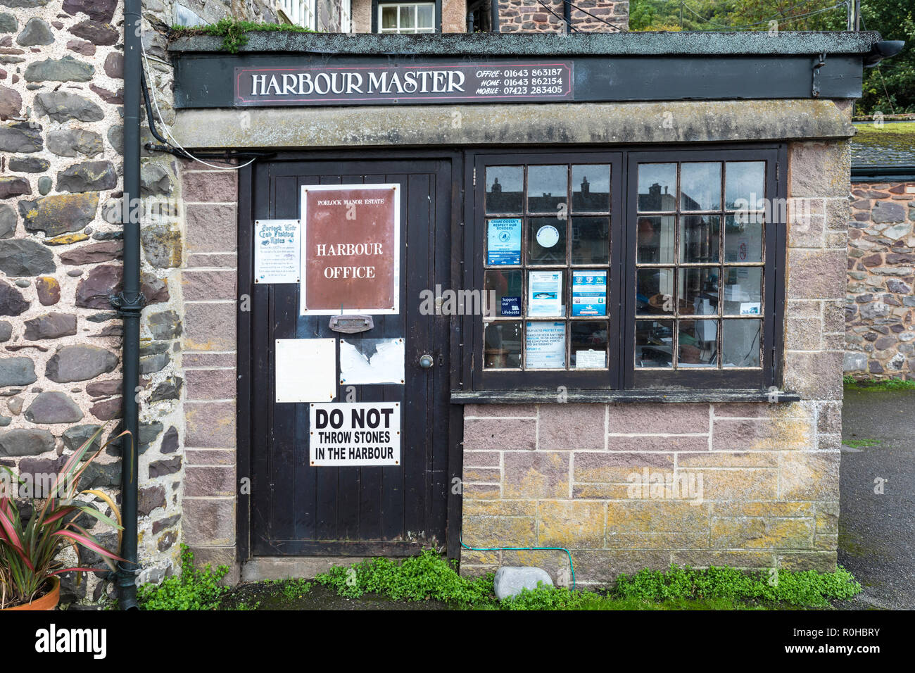 Harbour Master office with do not throw stones in the harbour sign, Porlock Weir, Devon, UK - Stock Image