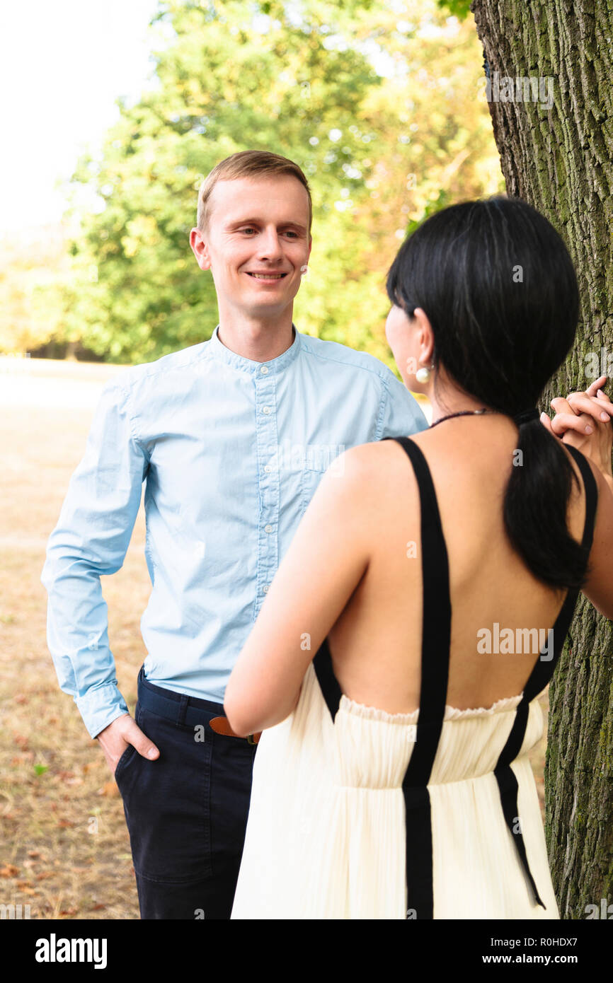 Attractive multiracial couple in summer park walking happily - Stock Image