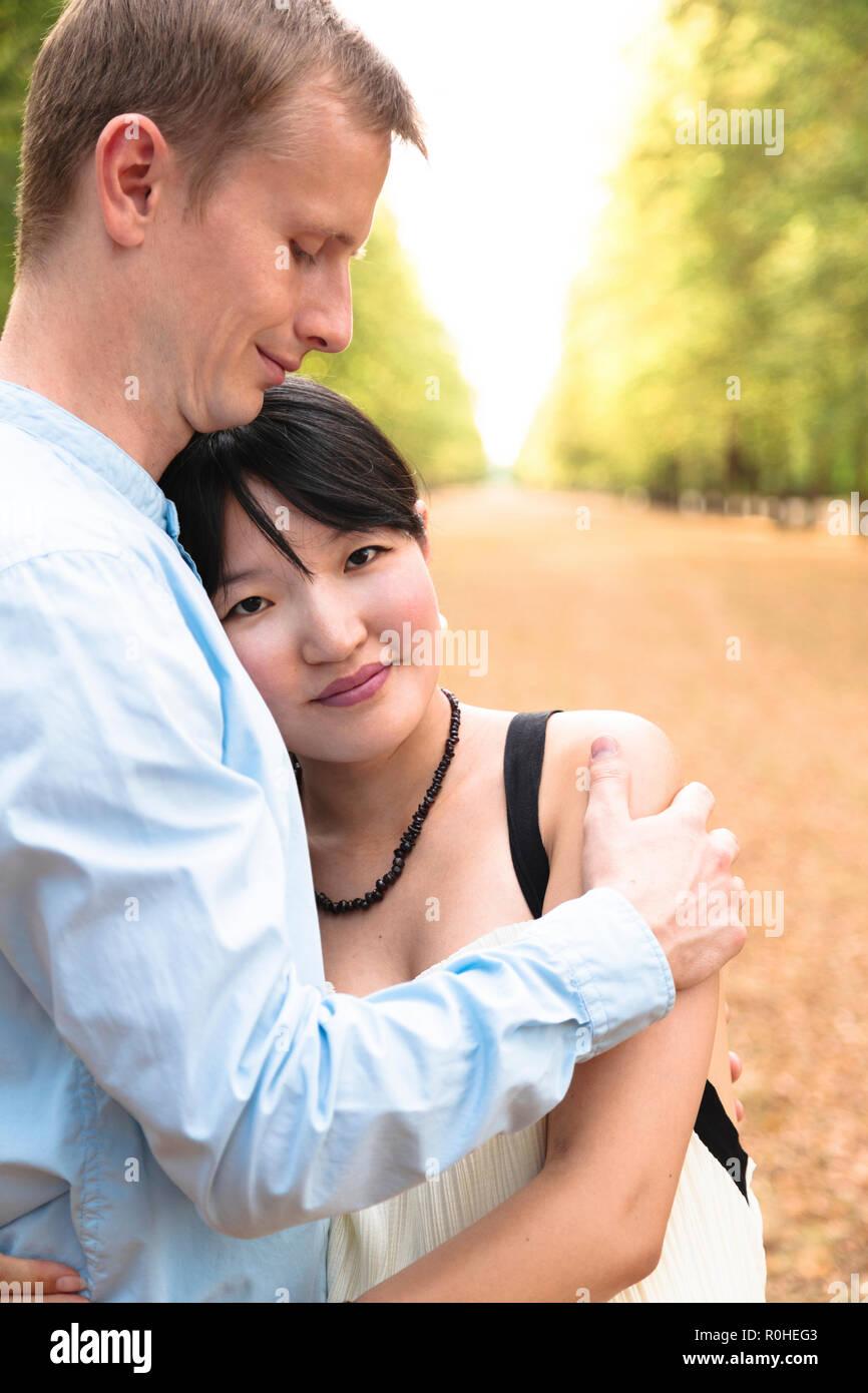 https://c8.alamy.com/comp/R0HEG3/romantic-international-couple-in-beautiful-park-hugging-each-other-R0HEG3.jpg