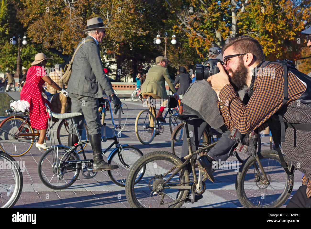 Washington DC, USA. 4th Nov 2018. Photographer at work during DC's 2nd Tweed Ride event. The Ride of cyclists who refuse to endure anymore spandex and feel great to spin through our beautiful streets in the finest most dapper attire. Credit: Andrei Medvedev/Alamy Live News - Stock Image