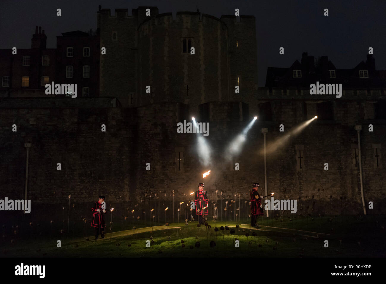 London, UK.  5 November 2018. Yeoman Warders, former servicemen and women, ceremonially light the first flame followed by volunteers proceeding to light the rest of the installation, gradually creating a circle of light.   A new installation by designer Tom Piper called 'Beyond the Deepening Shadow: The Tower Remembers', is open for the public to view at the Tower of London until Armistice Day 2018.  The moat is filled with thousands of individual flames commemorating the centenary of the end of the First World War. Credit: Stephen Chung/Alamy Live News - Stock Image