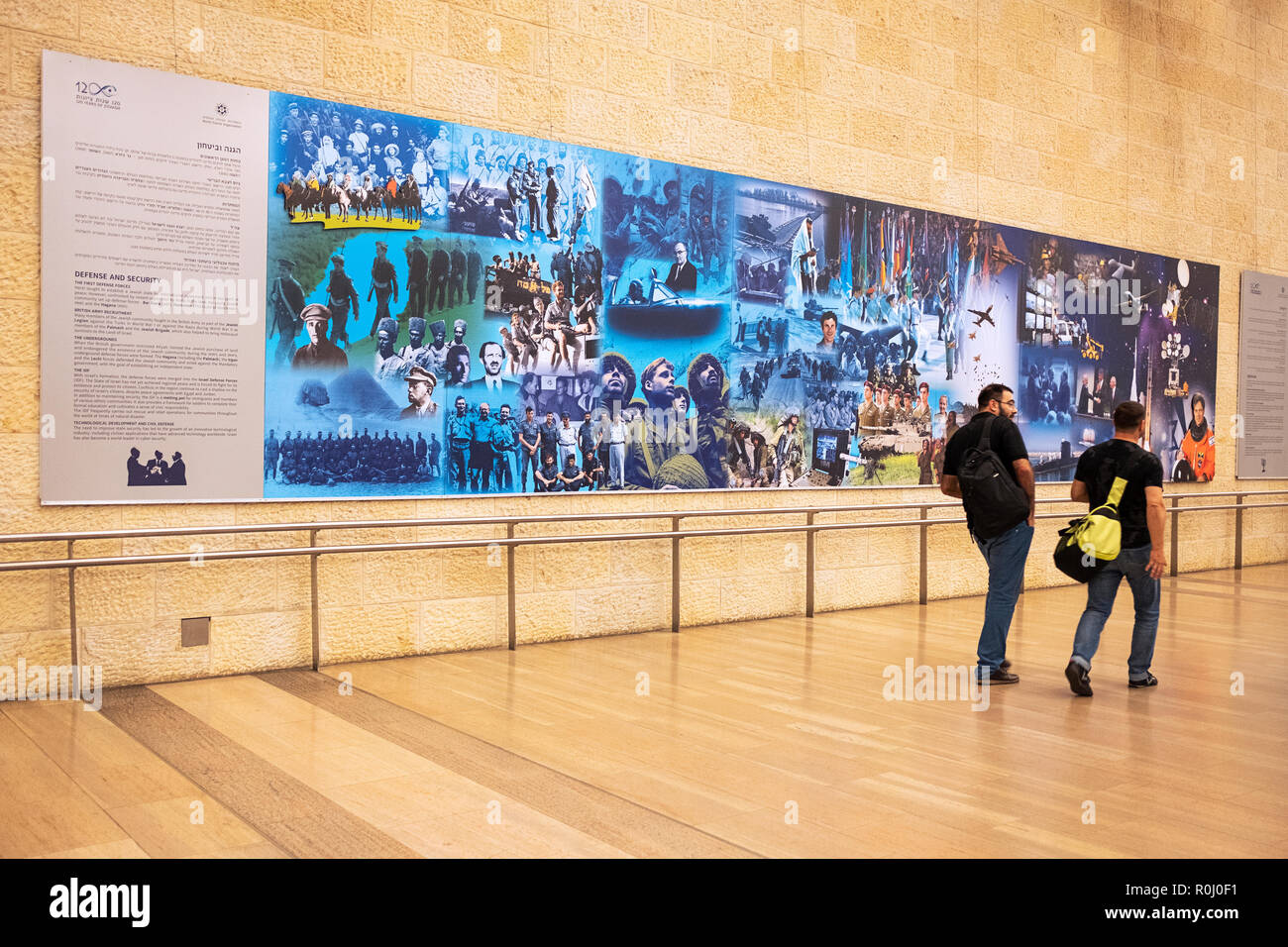 Two travelers pass one of the '120 Years of Zionism' murals at Ben Gurion Airport in Tel Aviv, Israel. - Stock Image