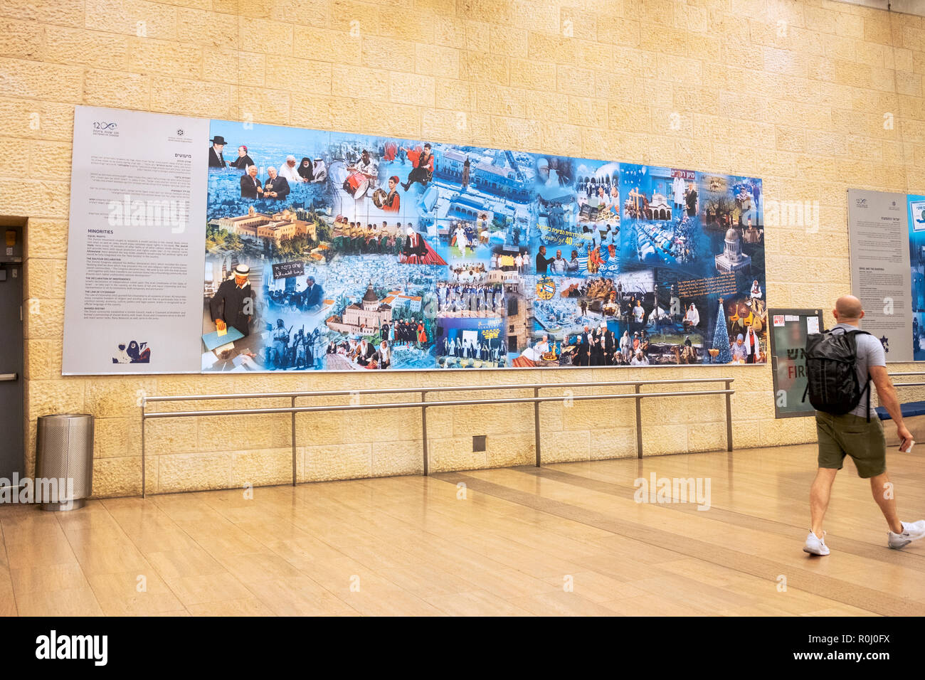 A traveler passes one of the '120 Years of Zionism' murals at Ben Gurion Airport in Tel Aviv, Israel. - Stock Image