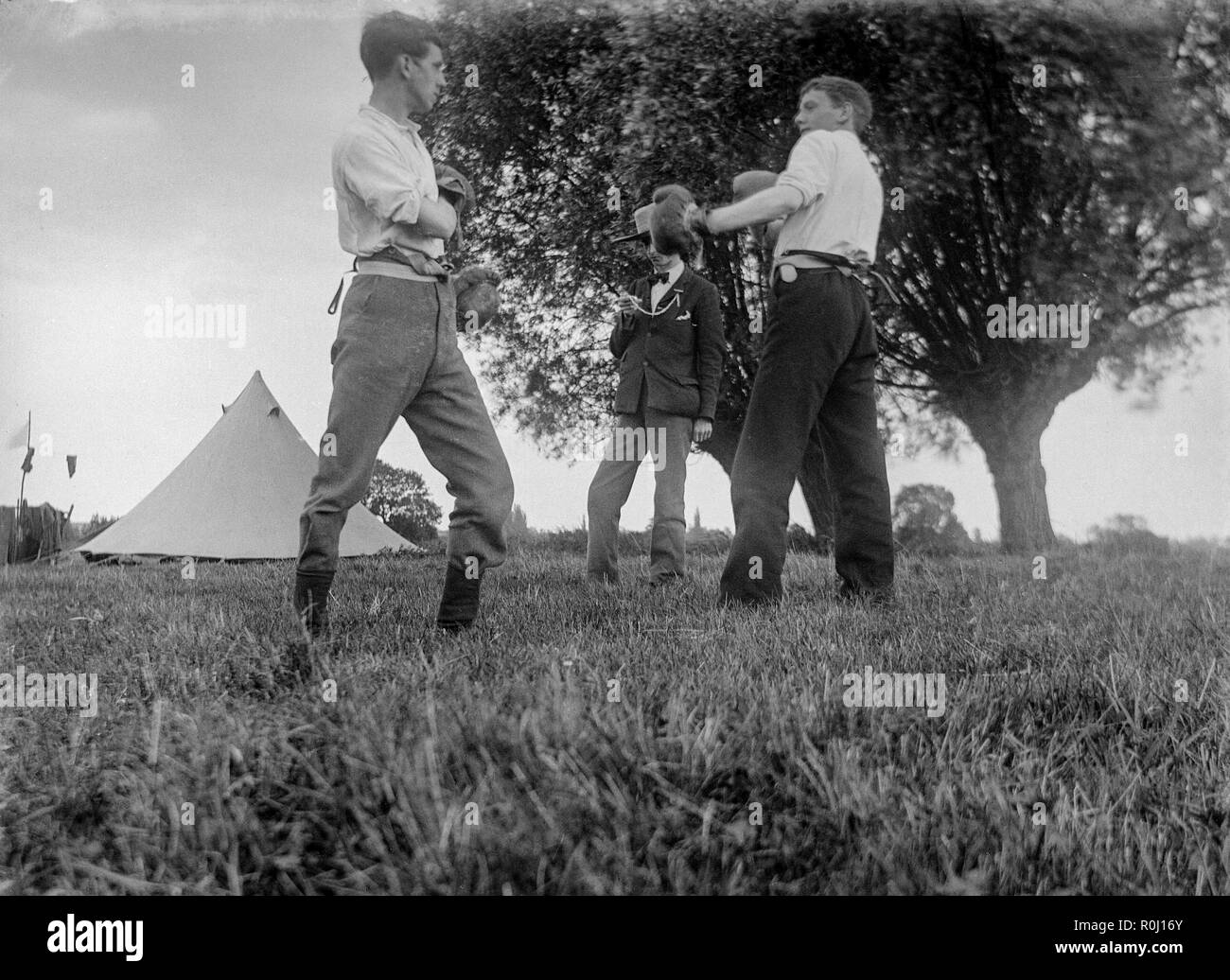 Edwardian black and white photograph showing two boys, or young men, on a camping trip in a field in England, squaring up for a boxing match, complete with vintage boxing gloves. A third boy acting as referee and timekeeper. - Stock Image