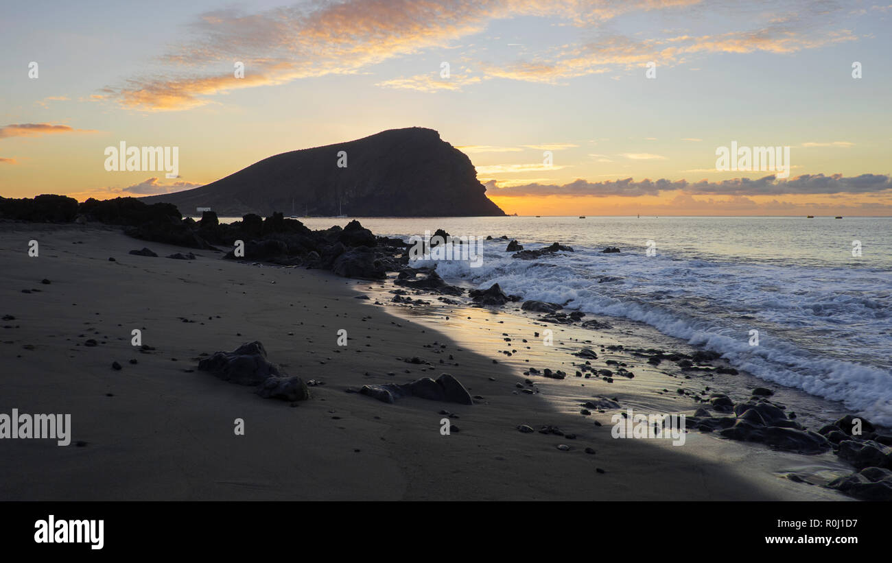 Dramatic sunrise at Montana Roja an unusual, stratovolcanic cone and La Tejita beach, one of the longest, natural beaches in Tenerife, Canary Islands - Stock Image