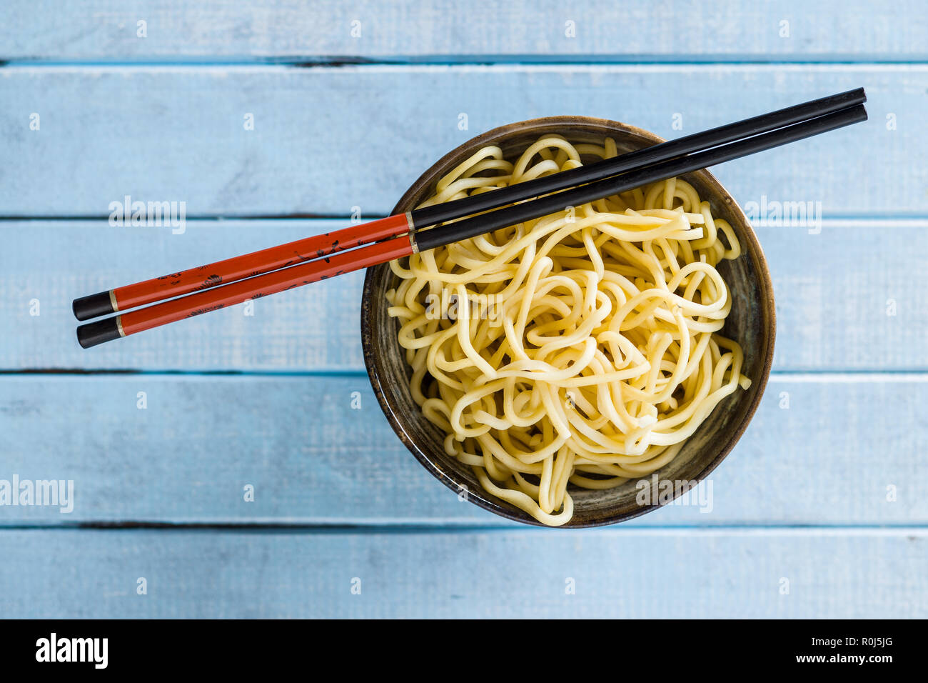 Cooked chinese noodles in bowl. Top view. - Stock Image