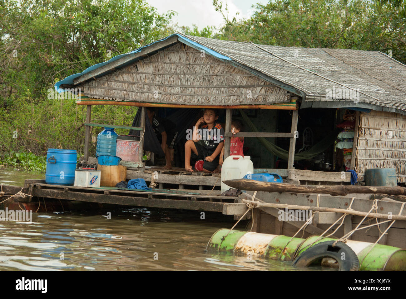 boy with football trikot in front of a house in a floating village on the tonle sap close to siem reap in cambodia - Stock Image