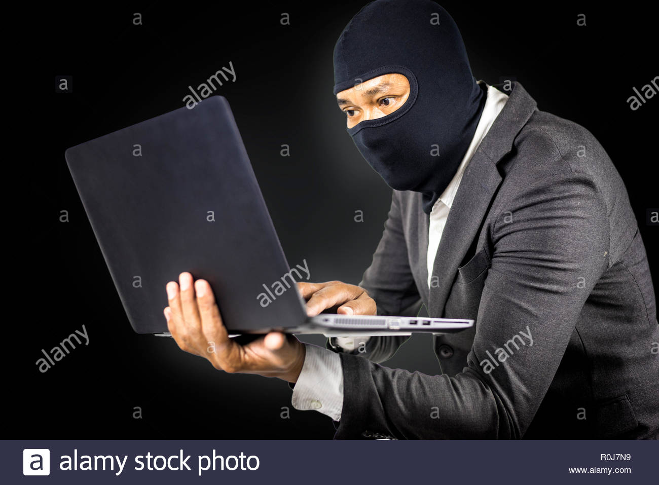 Data theft, Anonymous hacker with laptop on white isolated background, Cyber security concept - Stock Image