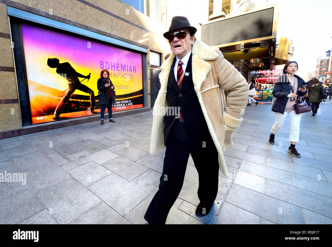 Man in a sheepskin jacket in Leicester Square, London, England, UK. - Stock Image