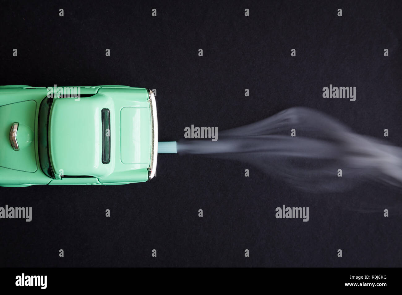 Flat Lay Of Car Toy Emitting Smoke Co2 From Exhaust Pipe On Dark