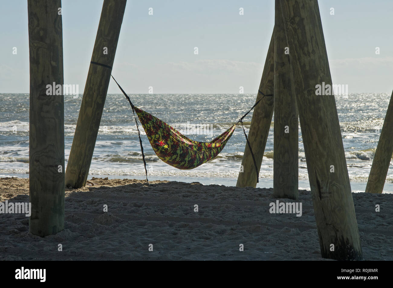 A person uses a hammock to spend a late November Day resting at the beach - Stock Image