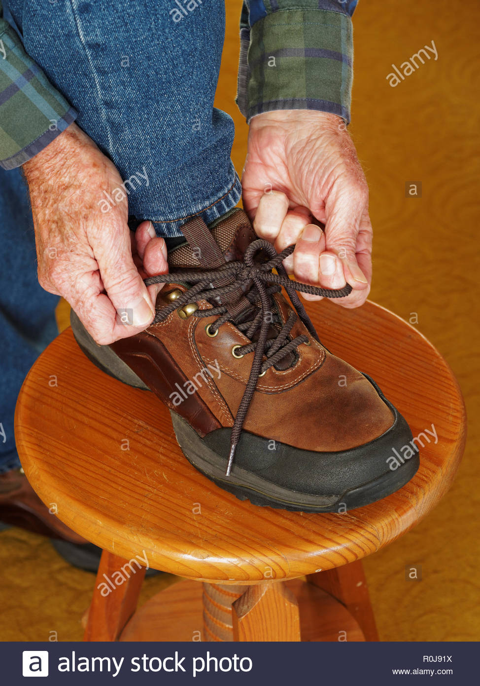Old man doing up shoelaces on brown hiking shoes - Stock Image