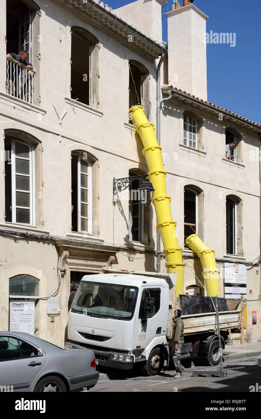 Rubbish Shoots and Builder's Truck in Use During Renovation or Construction Work on Run-Down or Old Building - Stock Image