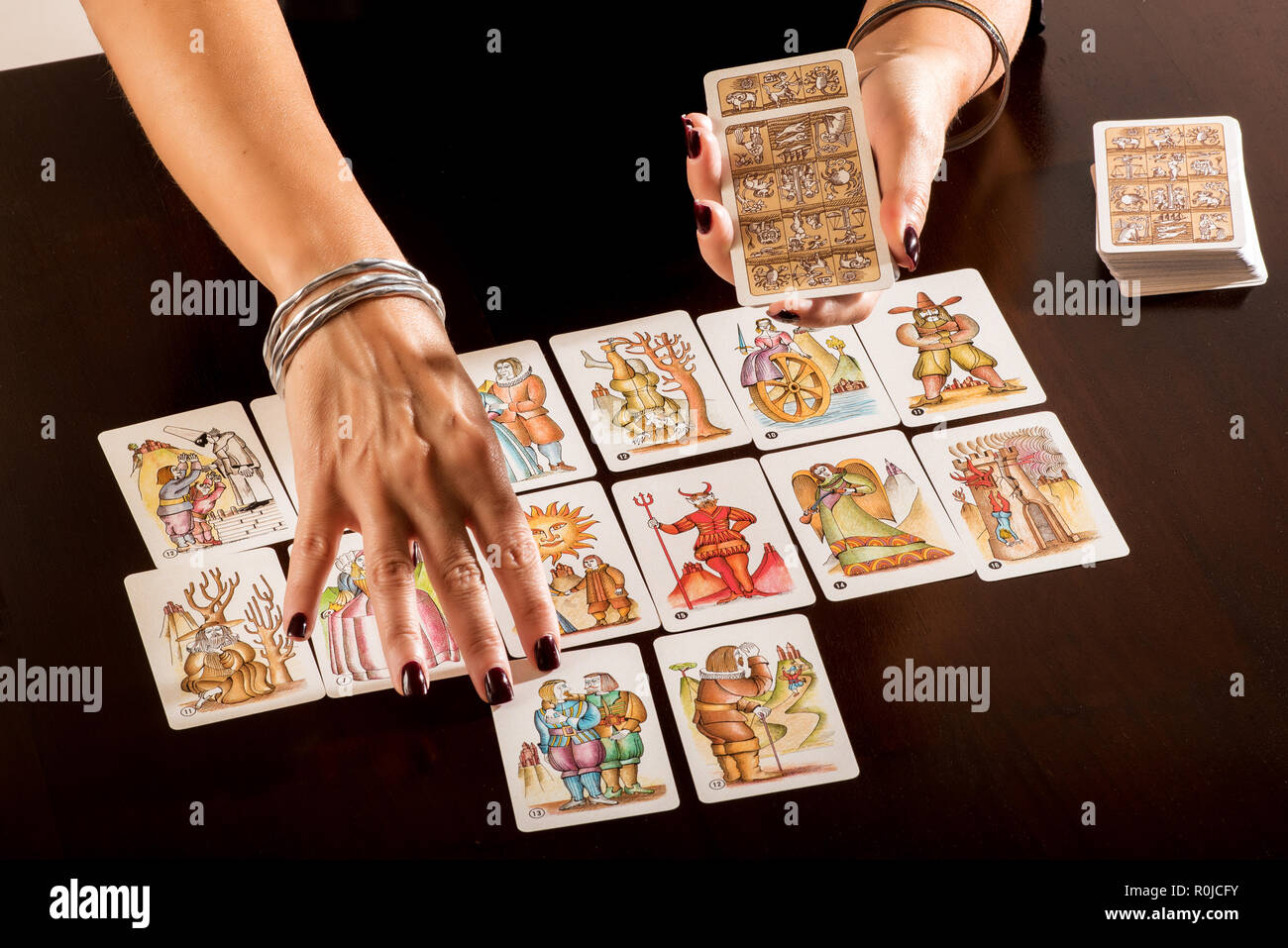 Fortune teller laying out a deck of tarot cards as she predicts the future for a client in a close up view on the pictorial allegorical cards and her  - Stock Image
