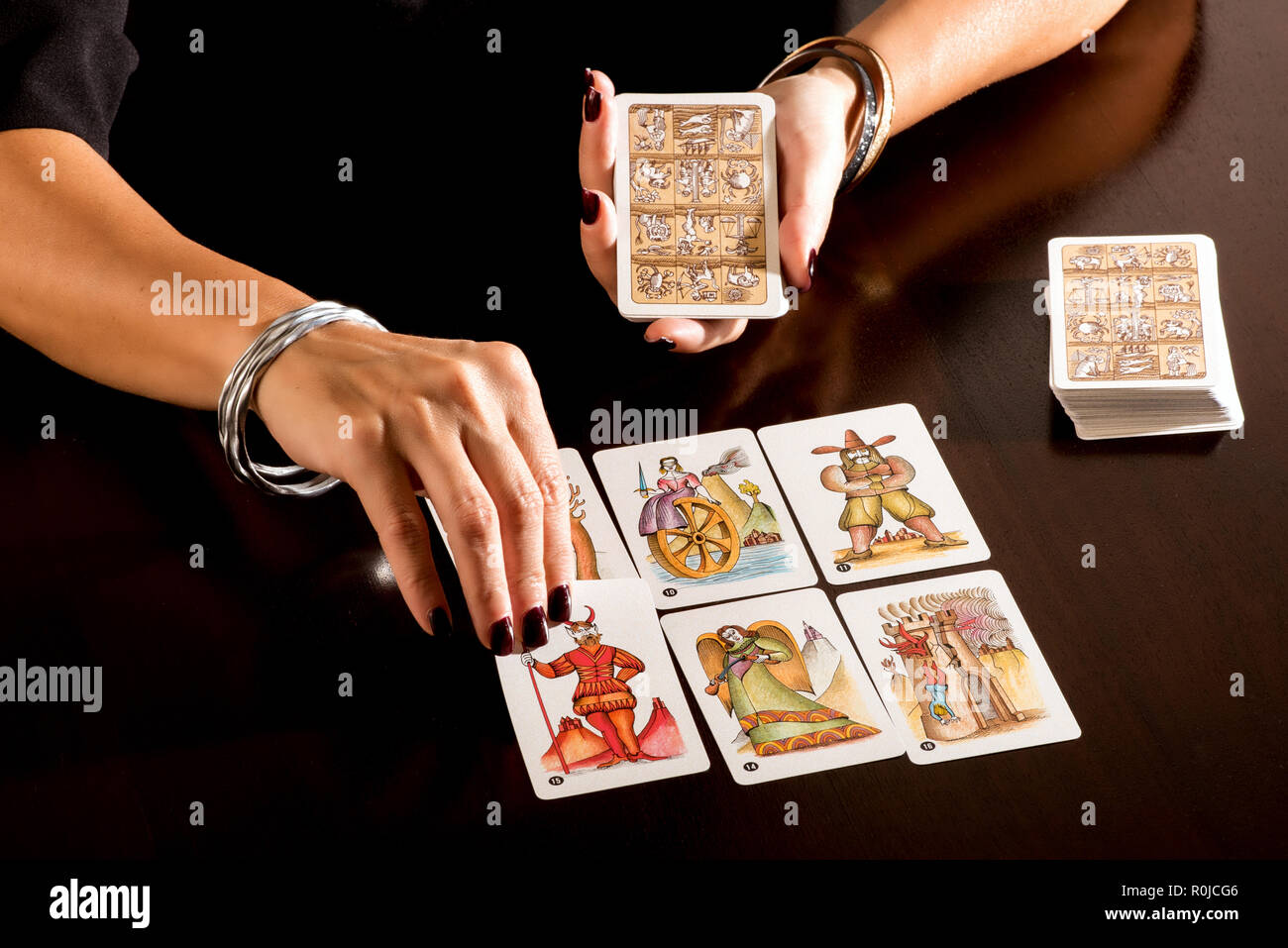 Fortune teller reading a deck of pictorial symbolic Tarot Cards in a close up on her hands laying them out on a table to make her prophesy - Stock Image