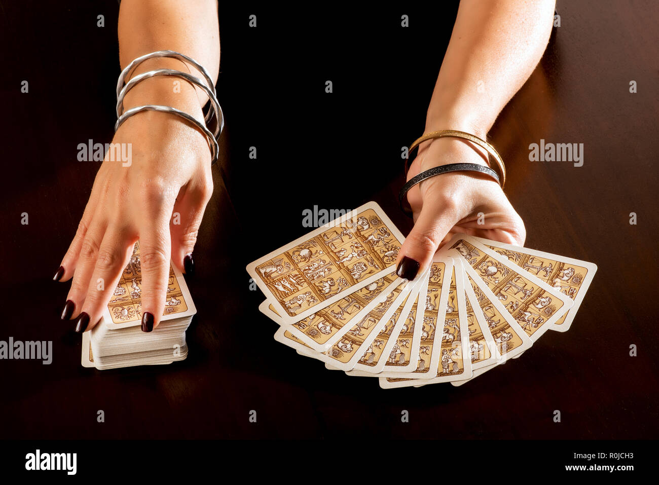 Fortune teller predicting the future with Tarot Cards holding them fanned out in her hand as she deals from a full deck in a close up on her hands - Stock Image