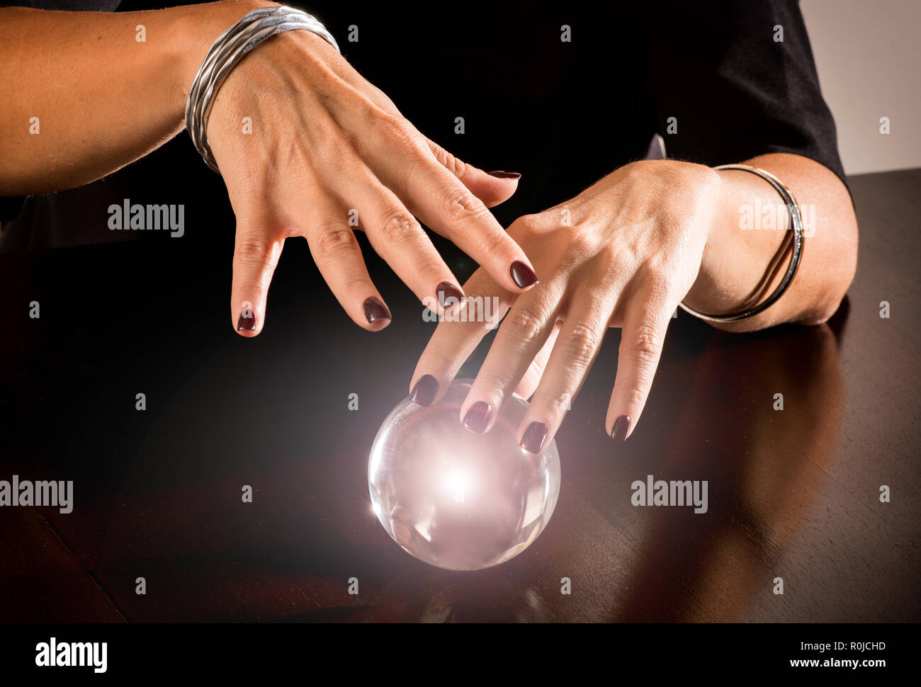 Fortune teller predicting the future on a magical glowing glass or crystal sphere in a close up view of her hands hovering over the orb - Stock Image