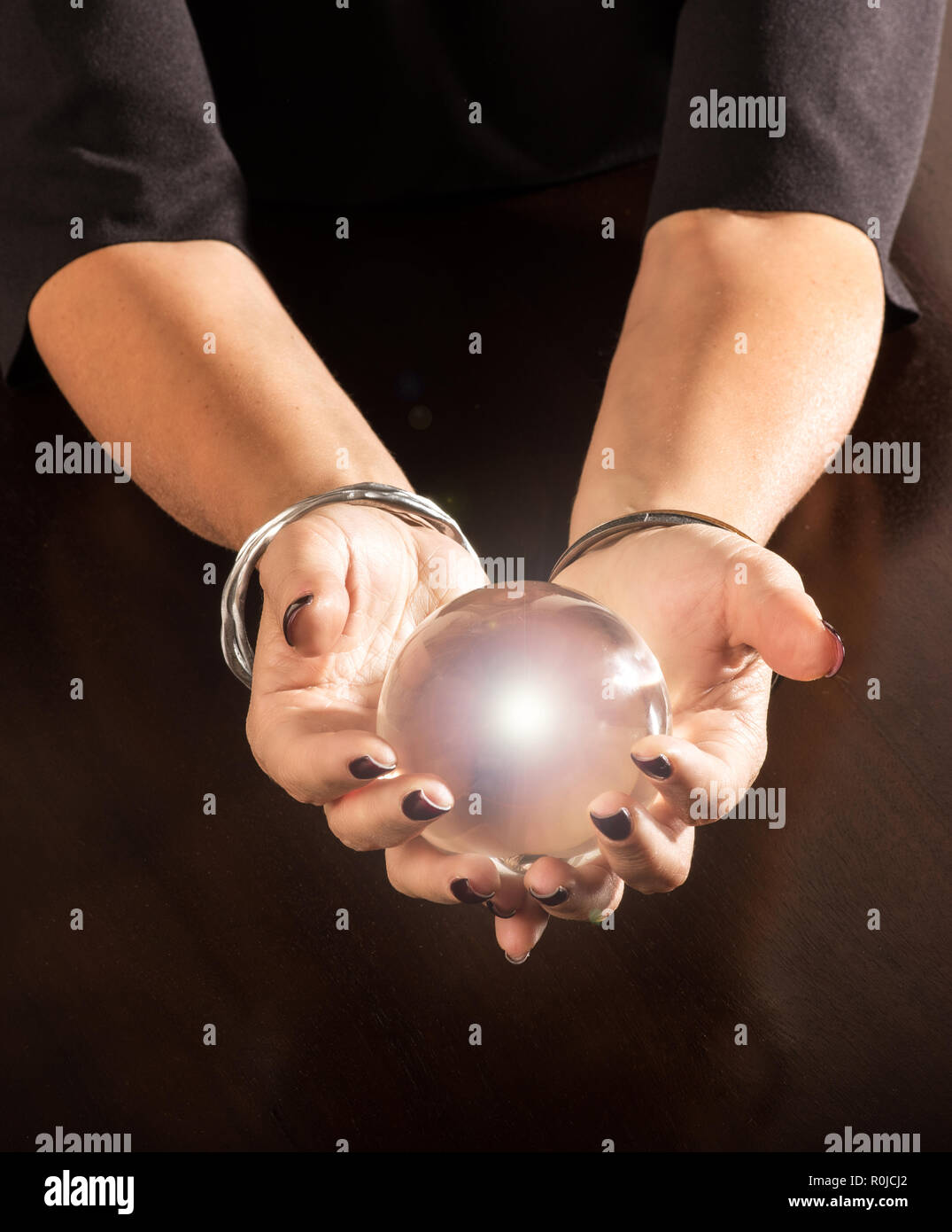 Fortune teller holding a magical glowing crystal ball cradled in her hands over a dark table with copy space below - Stock Image