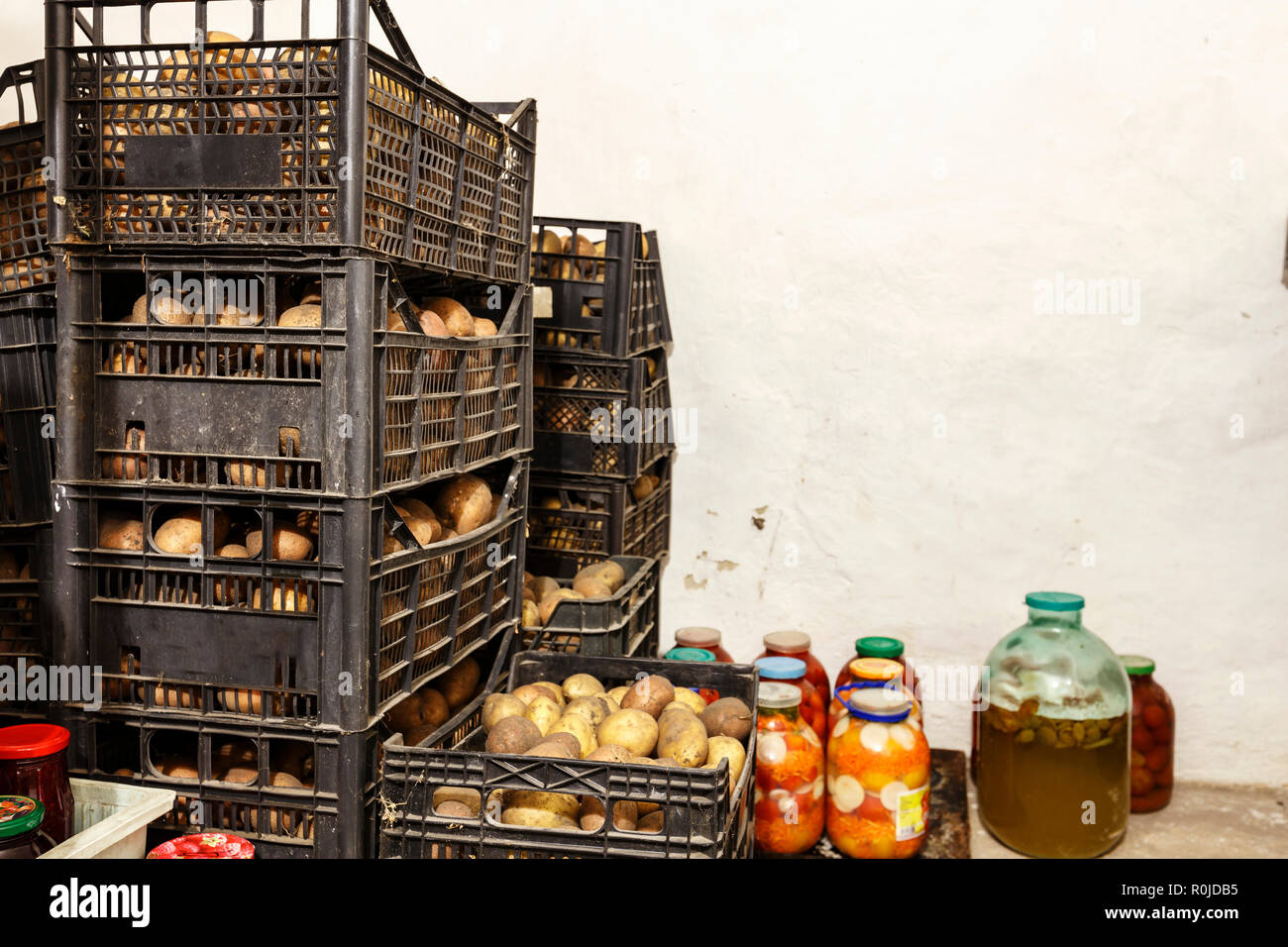 potatoes in boxes in the cellar. there are glass jars with conservation - Stock Image