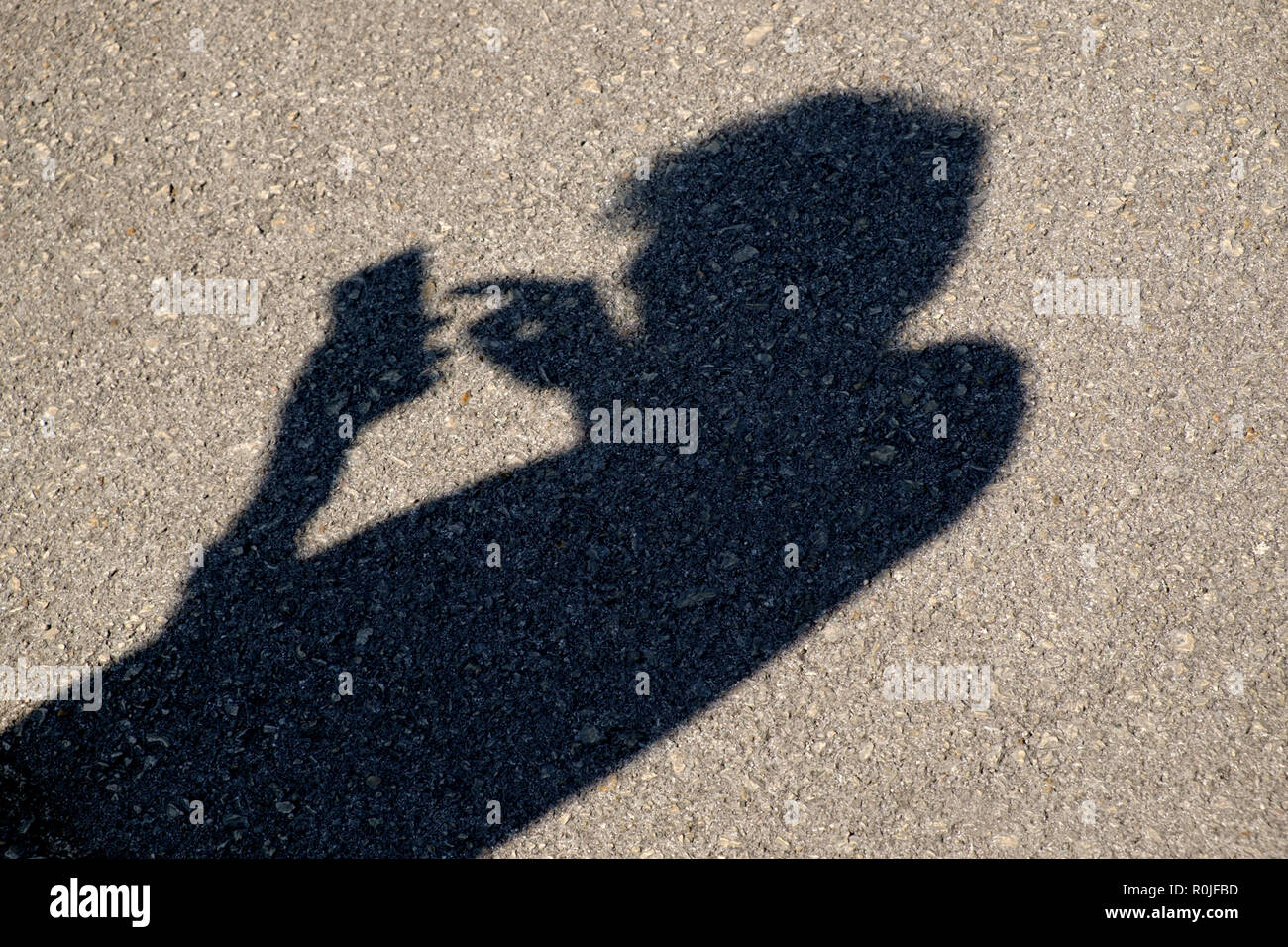 Shadow of a person using a smartphone with bad posture - Stock Image